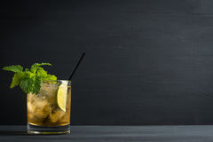 Old fashioned cocktail with lime and mint. On the wooden table royalty free stock image