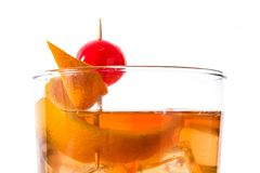 Old fashioned cocktail with orange and cherry isolated. Old fashioned cocktail with orange and cherry isolated on white background. Close up stock photography