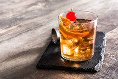 Old fashioned cocktail with orange and cherry on wood. En table. Copyspace stock image