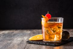 Old fashioned cocktail with orange and cherry. On wooden table. Copyspace stock image