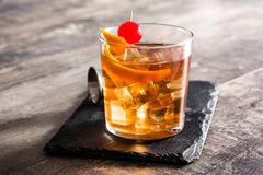 Old fashioned cocktail with orange and cherry on wood. En table royalty free stock image