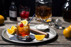 Old Fashioned Cocktail in Vintage Style Bar. An Old Fashioned cocktail in a vintage bar setting with the ingredients and tools in the background. Old Fashioneds Royalty Free Stock Photo