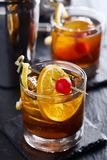 Old fashioned cocktails on cool slate garnished with orange slice, lemon peel, and cherry. Shot with selective royalty free stock image