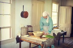 Old Fashioned Cook. One of the woman interpreters at Old World Wisconsin in Eagle, Wisconsin cooking in an old fashioned kitchen in period clothing Royalty Free Stock Image