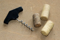 An old-fashioned corkscrew and three used corks on textured cardboard sheet Royalty Free Stock Image