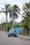 Old fashioned Cuban Car trough palms Stock Photos