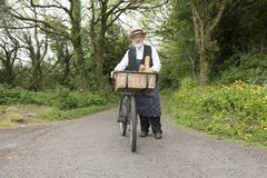 Old fashioned delivery man on a bicycle. In a rural setting stock photos
