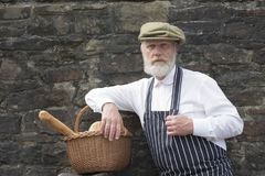 Old fashioned delivery man with a bread basket. With brick wall background stock image