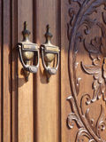 Old fashioned door knocker with carved door Royalty Free Stock Photos