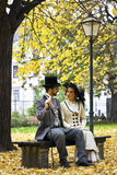 Old-fashioned dressed couple on a park bench in fall. Stock Images