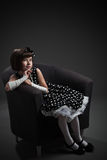 Old-fashioned dressed little girl sitting on chair Royalty Free Stock Photos