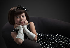 Old-fashioned dressed little girl sitting on chair Stock Photography