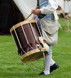 Old fashioned drum. A man in colonial times costume beats on an old fashioned drum stock images