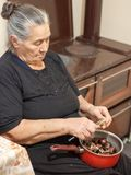 Old fashioned elder woman holding a pot with chestnuts and peeling them royalty free stock image