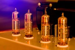 Old-fashioned electronic device amplifier with glowing bulb diode lamp for sound reproduction. Natural sound concept, Electronic vacuum tube or glowing tubes stock photo