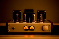 Old-fashioned electronic device amplifier with glowing bulb diode lamp for sound reproduction. Natural sound concept, Electronic vacuum tube or glowing tubes stock photography