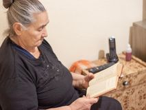 Old fashioned eler woman reading a book royalty free stock photo