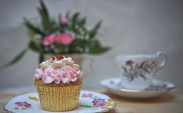 Food photography of a home made cupcake with pink butter cream topping and blurred floral background with cup and saucer. An old fashioned English image with Royalty Free Stock Images