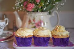 Food photography with homemade cupcakes with butter cream topping and floral background. An old fashioned English image with home made vanilla cup cakes with a Royalty Free Stock Photo