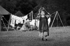 Old fashioned farm family. A mother  demonstrates farm life from the past at the Heston steam days in Heston Indiana. she hangs the laundry on a line outdoors Stock Photography