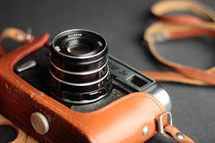 Old fashioned film camera. Very old fashioned film camera in leather case on strap Royalty Free Stock Images