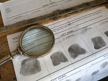 Old fashioned finger printing. Items including paper with prints and magnifying glass stock photos