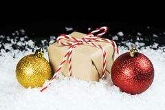 Old fashioned gift wrapped in plain paper, tied with red and white twine sitting in snow beside holiday ornaments. Black background with space for text royalty free stock photography