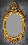 Old-fashioned gilt frame for a mirror on a concrete wall. Old-fashioned oval gilt frame for a mirror on a gray concrete wall Royalty Free Stock Photos