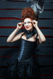 Old-fashioned girl in a corset and high hairdo. Royalty Free Stock Image