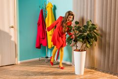 Old-fashioned girl in red dress watering plant with watering can. At home stock image