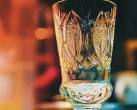 Old fashioned glass. Vintage crystal glass on a multicolored background Royalty Free Stock Photo