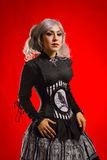 Old-fashioned gothic girl. Pretty gothic girl with black eyes standing over red background Royalty Free Stock Image