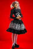 Old-fashioned gothic girl. Pretty gothic girl with black eyes standing over red background Royalty Free Stock Photography