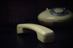 Old-fashioned handset and phone on a dark wooden background. hor Stock Image