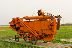 An old-fashioned harvester on display in saskatchewan. Antique farming equipment on display at an outdoor museum in the canadian priaires Royalty Free Stock Photography