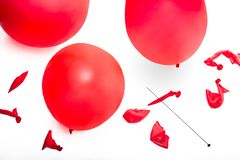 Old fashioned hat pin and a collection of popped and inflated red balloons. stock image