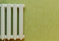 Old-fashioned heat radiator. Retro heat radiator against the green wall Royalty Free Stock Photos