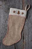 Old Fashioned Christmas Stocking. An old fashioned homemade rustic burlap Christmas Stocking on a rough wood surface Stock Images