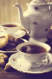 Old-fashioned image with two cups of tea vintage effect with cookies. Old-fashioned porcelain two cups of tea with cookies in vintage style with cookies stock image
