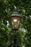 Old fashioned iron street lamp on The Mall in central London, lit up at dusk. Old fashioned iron street lamp on The Mall in central London, England, lit up at Royalty Free Stock Photography