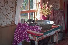 Old Fashioned Ironing Board. An old fashioned ironing board, iron, and washtub sitting on an old table in front of an open window with a vase of wildflowers royalty free stock image