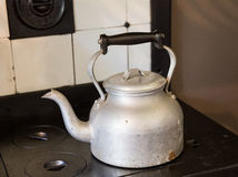 Old fashioned kettle on hob. Old fashioned metal kettle sitting on cast iron black cooker hob with tiled surround stock images