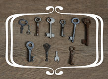 Old fashioned keys on wooden aged background with frame concept Royalty Free Stock Photography