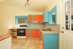 Old fashioned kitchen interior with orange and blue cabinets. Stock Photos