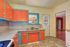 Old fashioned kitchen interior with orange and blue cabinets. Royalty Free Stock Image