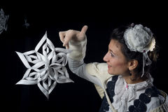 Old fashioned lady playing with a paper handcrafted snowflake Royalty Free Stock Photography