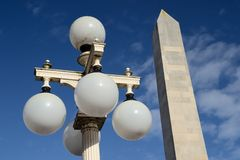 Old fashioned lamp with monument in background. Royalty Free Stock Images