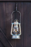Old fashioned lantern on a brown wooden wall Stock Image
