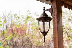 Beautiful old-fashioned lantern hanging on a wooden veranda at the garden house royalty free stock photos