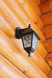 Old-fashioned lantern on logs wall Stock Image